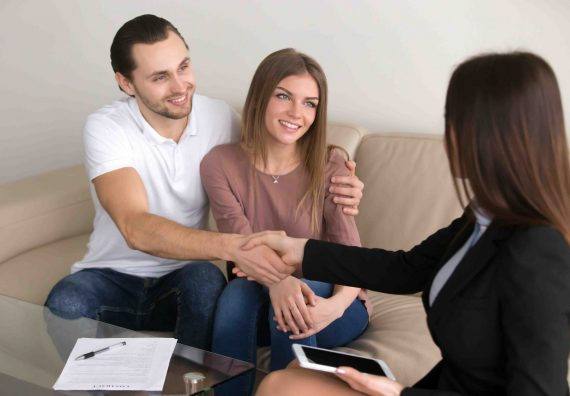 Cheerful young couple shaking hands with bank worker after signing loan contract, banking credit approval, personal insurance, legal assistance, lease agreement, mortgage investment